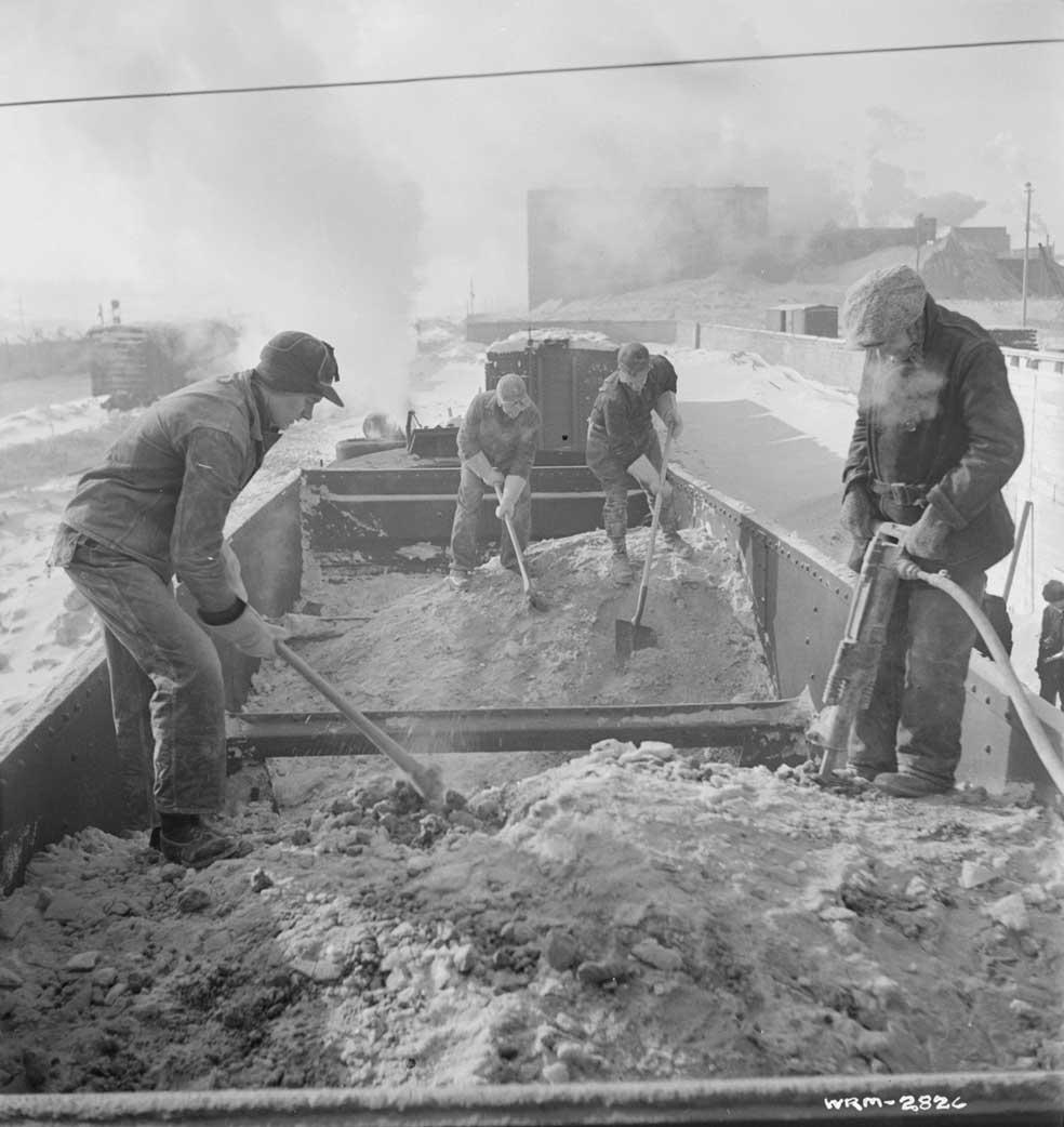 Des ouvriers forent de la bauxite dans des wagons